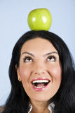 Surprised woman hold an apple on head stock images