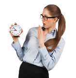 Surprised woman holding an alarm clock in a hand Stock Images
