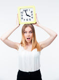 Surprised woman holding big clock. Isolated on a white background. Looking at camera Stock Photos