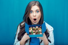Surprised woman holding blue box with chocolate candy. Blue wall background royalty free stock images