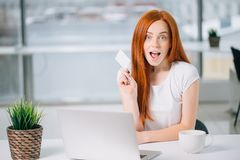 Surprised woman holding credit card, and make online payment by plastic card. Beautiful surprised and successful woman holding credit card, and make online Stock Photos