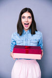 Surprised woman holding gift and looking on camera Royalty Free Stock Photos