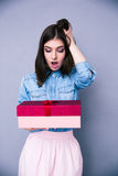 Surprised woman holding gift Stock Images