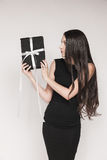 Surprised woman holding gift. Young beautiful woman with long hair wearing black cocktail dress is holding elegantly wrapped gift. Surprised woman is happy to Stock Images