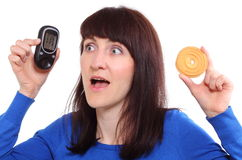 Surprised woman holding glucose meter and cake Stock Image