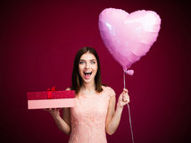 Surprised woman holding heart shaped balloon and gift box Royalty Free Stock Image