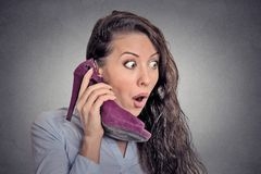 Surprised woman holding high heeled shoe in hand as phone Stock Photos