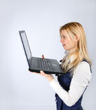 Surprised woman holding a laptop in hand royalty free stock images