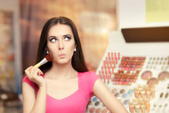 Surprised Woman Holding a Make-up Brush Royalty Free Stock Image