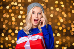 Surprised woman holding present box and talking on the phone Stock Photo