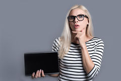 Surprised woman holding the tablet. Impressive qualities of modern devices. Puzzled young woman holding the tablet and raising one hand to her opening mouth Royalty Free Stock Images