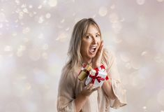 Surprised woman holding some Christmas gifts Stock Images