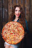 Surprised woman holds large pizza. Food delivery promotion. Stock Image