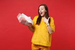 Surprised woman keeping mouth open, hold red striped present box with gift ribbon isolated on red background. Valentine royalty free stock image