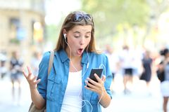 Surprised woman listening to music watching online content. Surprised woman listening to music and watching online content in a smart phone in the street Royalty Free Stock Photos