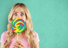 Surprised woman with lollipop candy over green background Royalty Free Stock Image