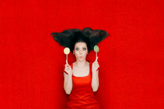 Surprised Woman With Lollipops on Red Background. Funny girl elegant red dress holding candy Stock Photos