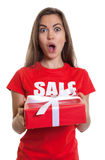 Surprised woman with long brown hair and gift sale in shirt Royalty Free Stock Photography