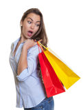 Surprised woman with long dark hair and shopping bags. On an isolated white background for cut out Royalty Free Stock Photography