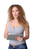 Surprised woman with long red curly hair and tablet in hands Stock Image