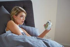 Surprised woman looking at alarm clock Stock Image