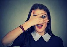Surprised woman looking between fingers Stock Image
