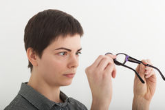 Surprised woman looking at her glasses. Stressed shocked businesswoman. Negative human face expressions, emotion feeling Royalty Free Stock Images