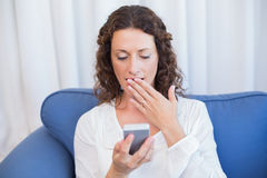 Surprised woman looking at her mobile phone. In the living room Royalty Free Stock Images