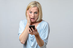 Surprised woman looking at her mobile phone Royalty Free Stock Image