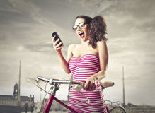 Surprised woman looking at her phone Stock Photography