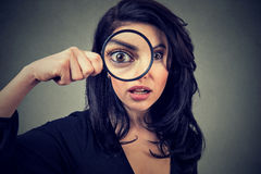 Surprised woman looking through magnifying glass. Isolated on gray wall background Stock Photos