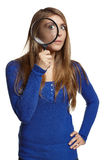 Surprised woman looking through the magnifying glass at you. Over white background Royalty Free Stock Photography