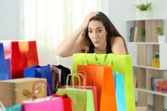 Surprised woman looking at multiple purchases. In colorful shopping bags at home stock image