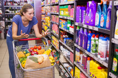 Surprised woman looking at product on shelf Stock Photos