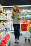 Surprised woman looking at product while standing with food trolley Royalty Free Stock Photo