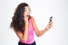 Surprised woman looking on smartphone Stock Image