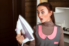 Surprised woman looking at the sole of the iron Royalty Free Stock Photography