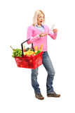 Surprised woman looking at store receipt. Full length portrait of a surprised woman looking at store receipt and holding a shopping basket on white background stock photo