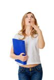 Surprised woman looking up, holding binder.  Stock Photography