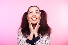 Surprised woman looking up. On pink background Royalty Free Stock Images