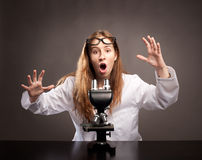 Surprised woman with microscope. Surprised young woman working with a microscope Stock Image