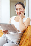 Surprised woman with newspaper Stock Image