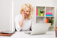 Surprised woman at the office using phone  and computer Stock Image