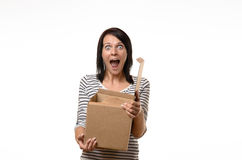 Surprised woman with open cardboard box. Front view of single surprised woman in striped shirt and brown hair holding an open cardboard box Royalty Free Stock Photos