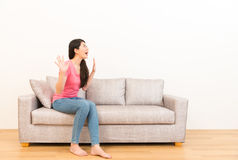 Surprised woman open the mouth excitedly. And looking at the white copyspace air open hands gestures to showing surprised sitting on the couch with white Stock Image
