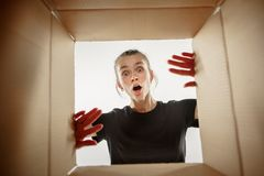 Woman unpacking and opening carton box and looking inside stock photo