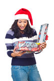 Surprised woman opening Christmas gift Stock Photo