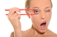 Surprised woman opens her eyes chopsticks. Isolated on white stock photography