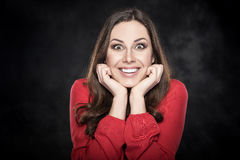 Surprised woman over dark background. Portrait of surprised smiling woman over dark background Stock Photo