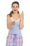 Surprised woman in pajamas with TV remote control Stock Photos
